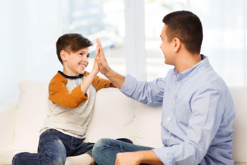 Père heureux et fils faisant la haute cinq à la maison images stock