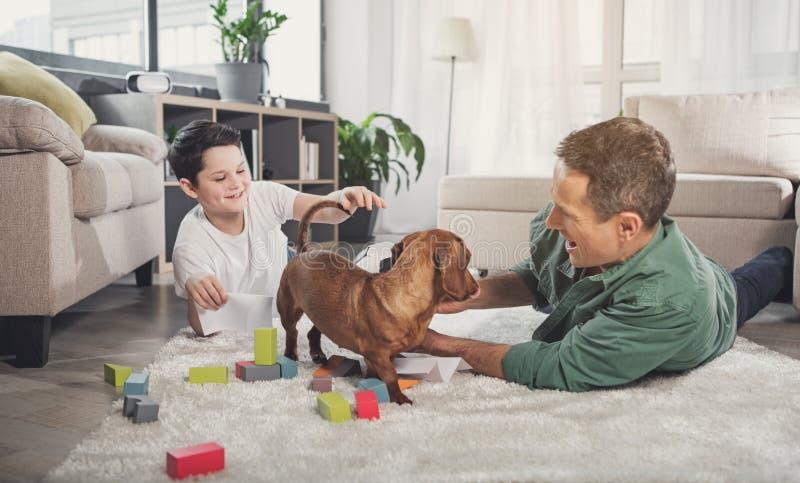 Père heureux et fils jouant avec le chien à la maison image stock