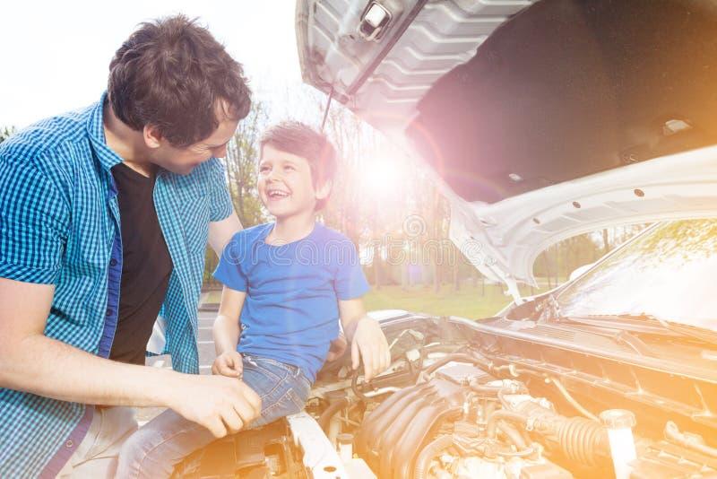 Père heureux et fils réparant la voiture dehors photo stock