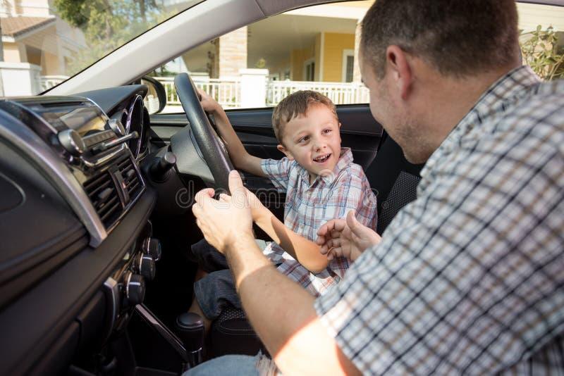 Père heureux et fils s'asseyant dans la voiture au temps de jour photos libres de droits