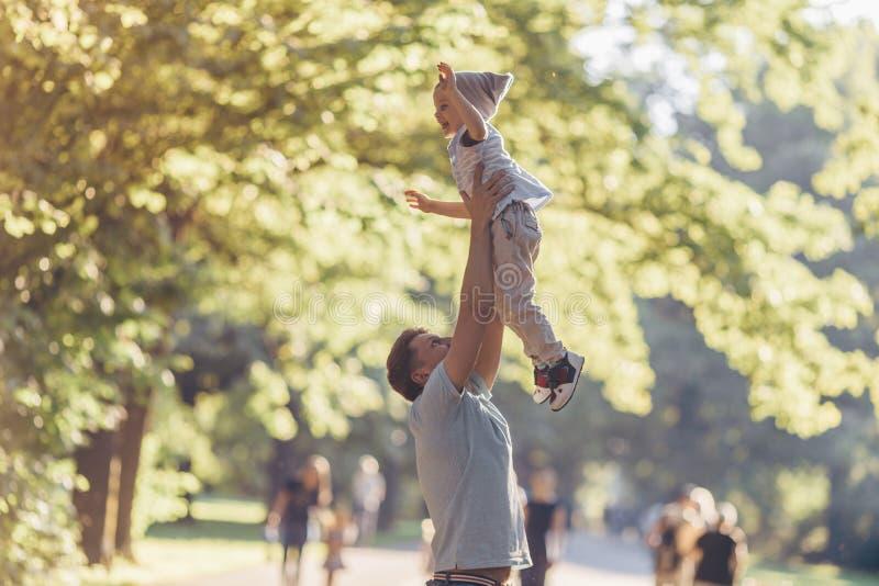 Père heureux et un petit fils dehors images stock