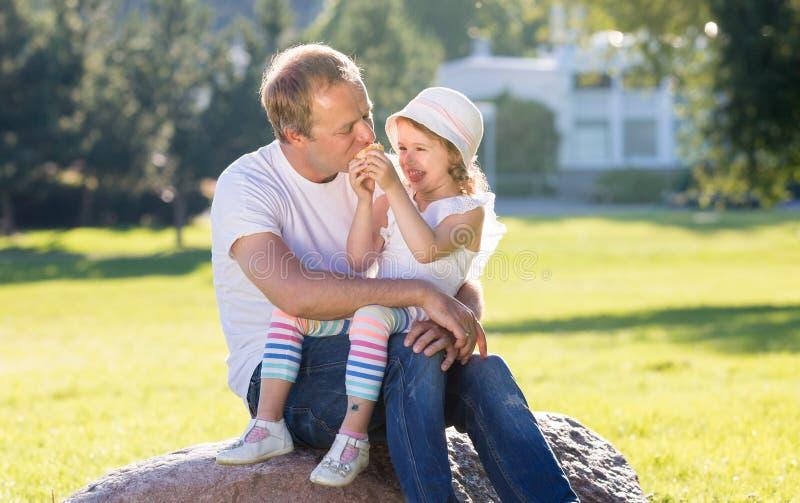 Père heureux jouant avec la petite fille mignonne, mangeant le sandwich image libre de droits