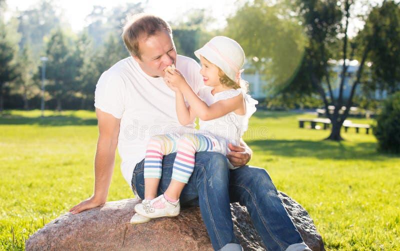 Père heureux jouant avec la petite fille mignonne, mangeant le sandwich image stock