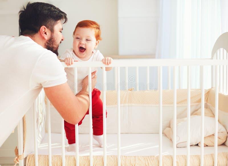 Père heureux jouant avec le bébé infantile dans le berceau à la maison image stock