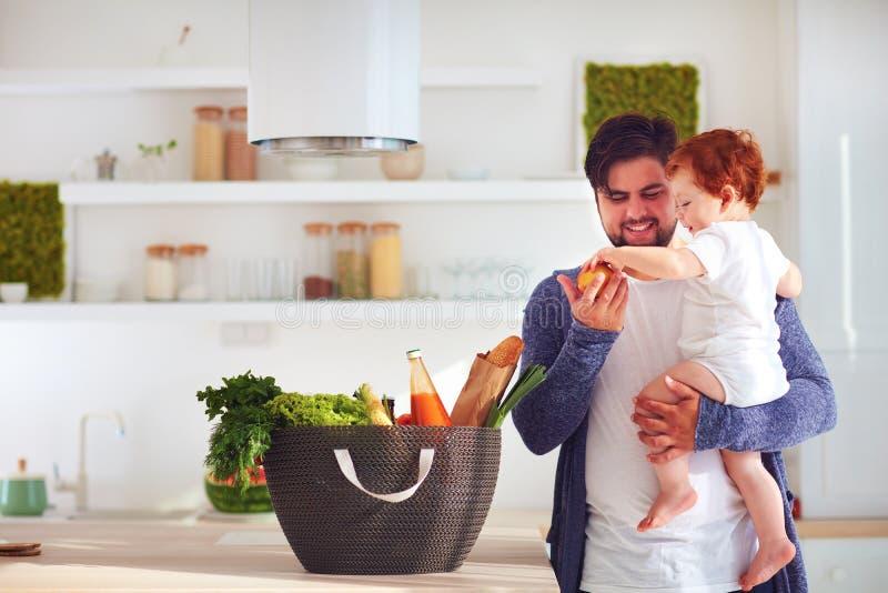 Père heureux offrant au fils infantile de bébé un fruit frais de panier à provisions, cuisine à la maison images stock