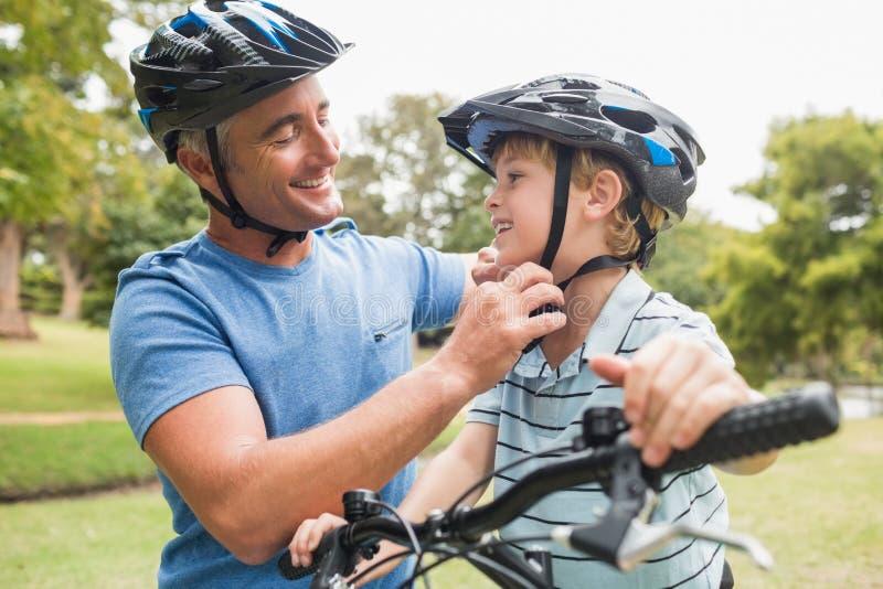 Père heureux sur un vélo avec son fils images stock