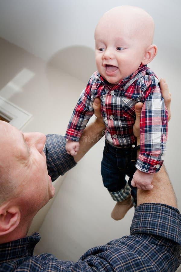 Père Holding Son dans le ciel images stock