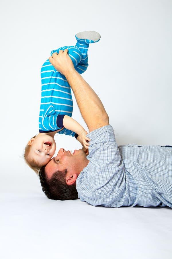 Père Holds Toddler Son à l'envers image libre de droits