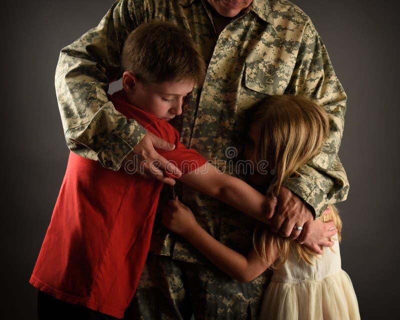 Père Hugging Family de soldat d'armée à la maison photographie stock libre de droits