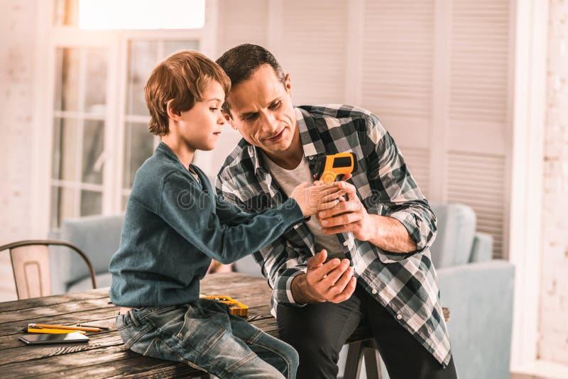 Père intéressé montrant à son fils quelques fonctions fraîches de son outil images stock