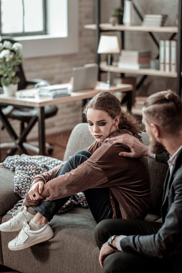 Père intéressé touchant l'épaule de sa fille déprimée image stock