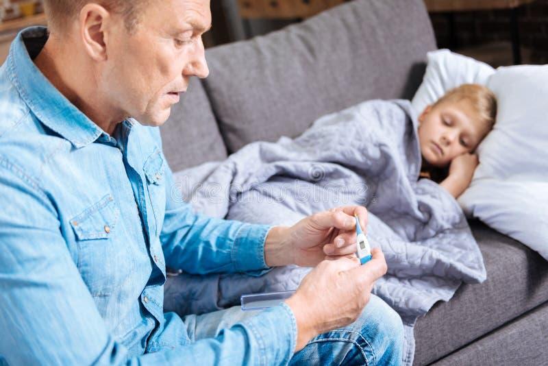 Père intéressé vérifiant la température de son fils malade photographie stock libre de droits