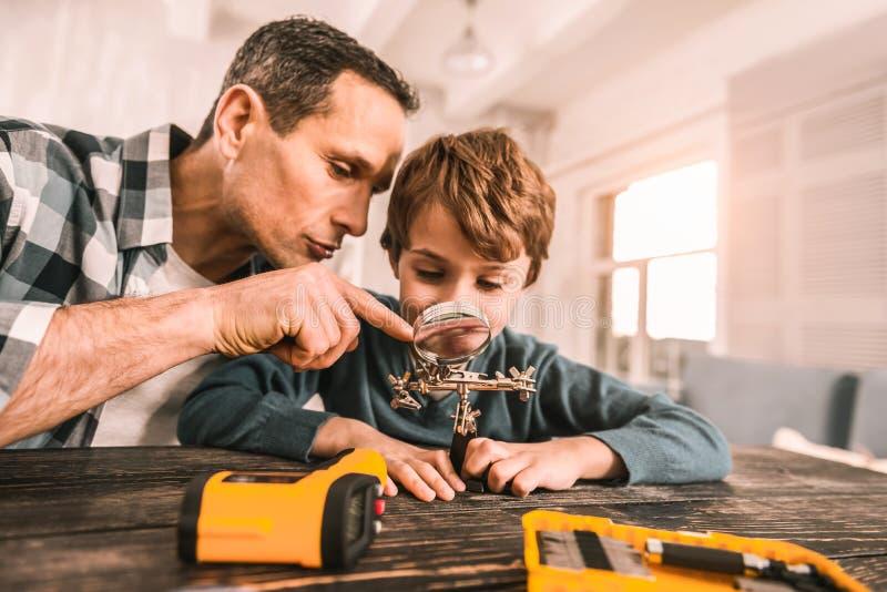 Père intelligent et fils fascinés par l'échelle des choses photos stock
