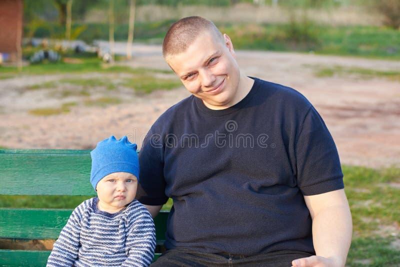 Père joyeux s'asseyant avec son fils contrarié sur un banc en parc photos stock