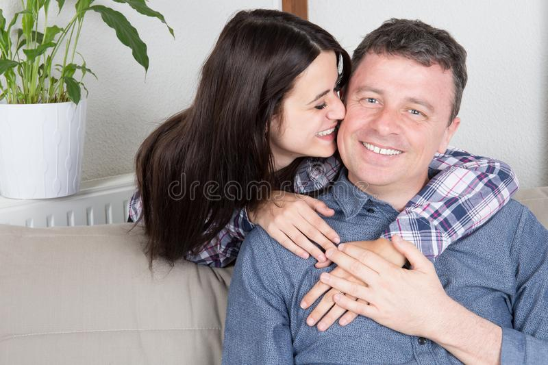 père joyeux s'asseyant dans le sourire à la maison de sofa et son baiser doux de fille photo stock