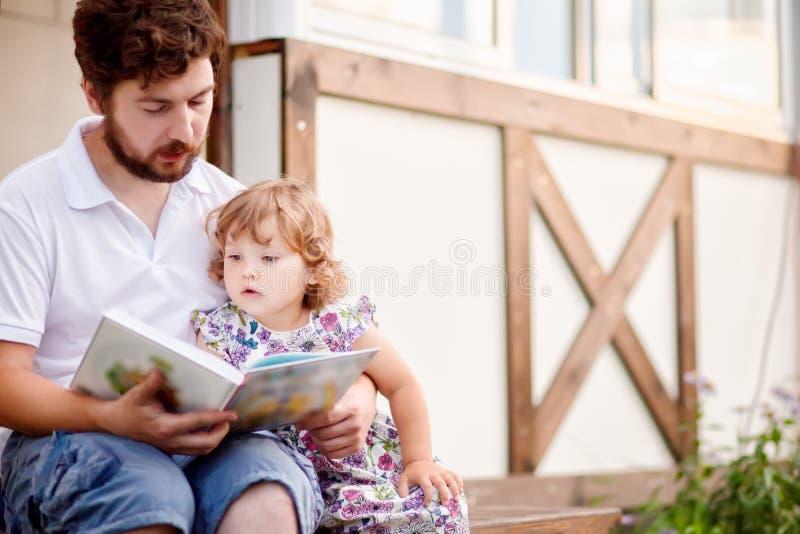 Père lisant à son enfant d'enfant en bas âge, extérieur photos libres de droits