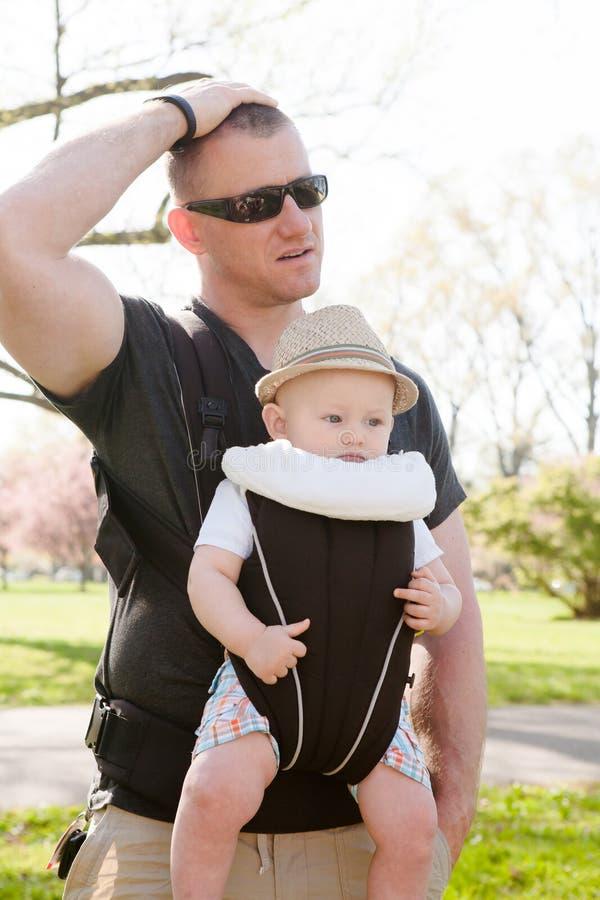 Père Lost ou renversement avec le fils dans le transporteur de bébé images stock