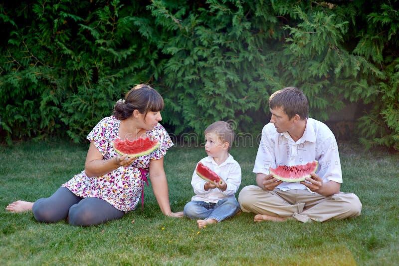 Père, mère et fils mangeant la pastèque se reposant sur l'herbe photographie stock