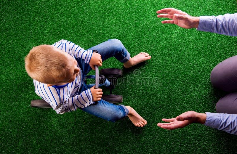 Père méconnaissable attrapant son fils montant un vélo images stock