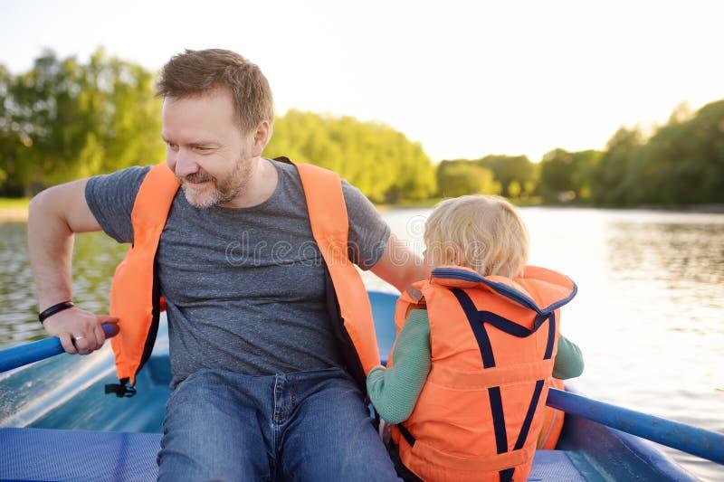 Père mûr et petit canotage de fils sur une rivière ou un étang au jour d'été ensoleillé Temps de famille de qualité ensemble sur  image libre de droits