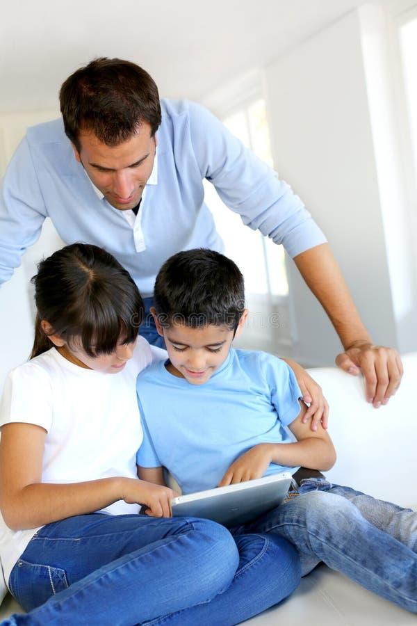 Père observant au-dessus des enfants tout en à l'aide du comprimé photo stock