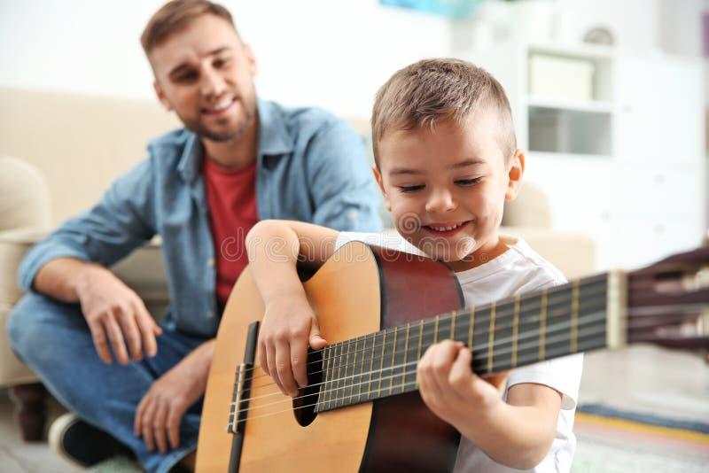 Père observant son fils jouer la guitare image stock