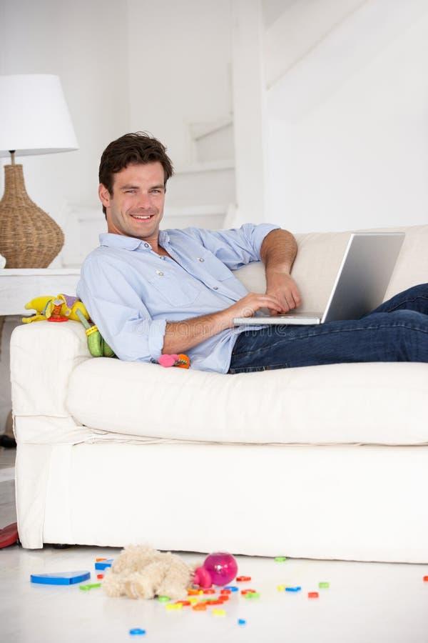 Père occupé travaillant à la maison sur l'ordinateur portatif photographie stock libre de droits