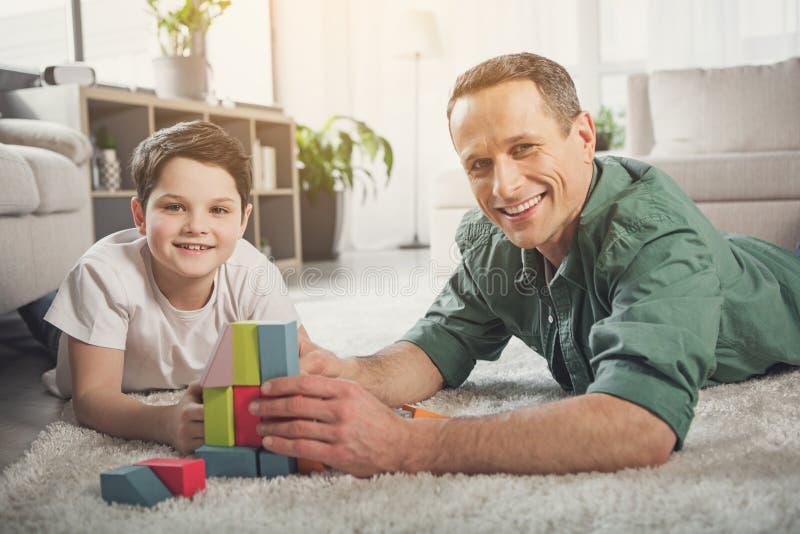 Père positif et fils appréciant le temps ensemble à la maison photo stock