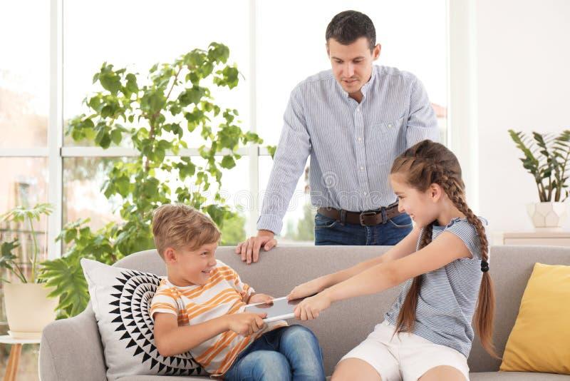 Père prenant le comprimé des enfants de combat photo stock