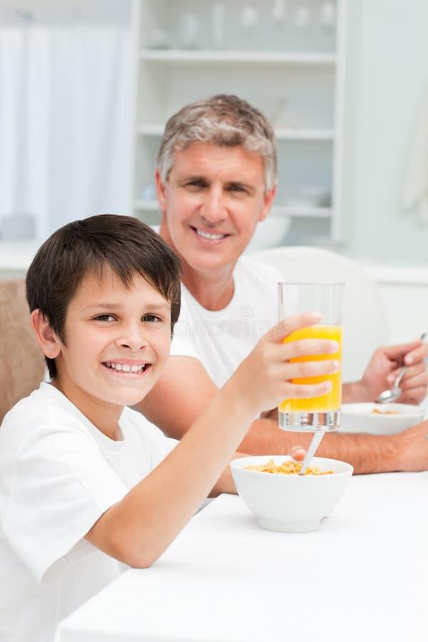 Père prenant son petit déjeuner avec son fils photos stock