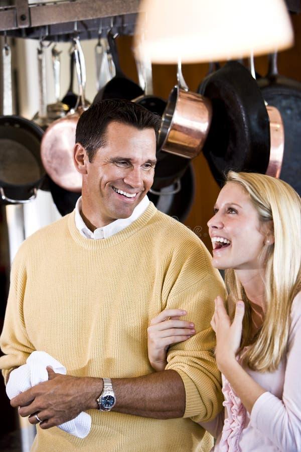 Père proche et descendant de l'adolescence riant dans la cuisine image libre de droits