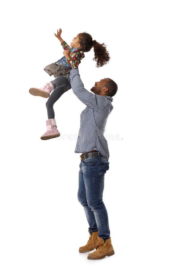 Père projetant le petit descendant dans le ciel images libres de droits