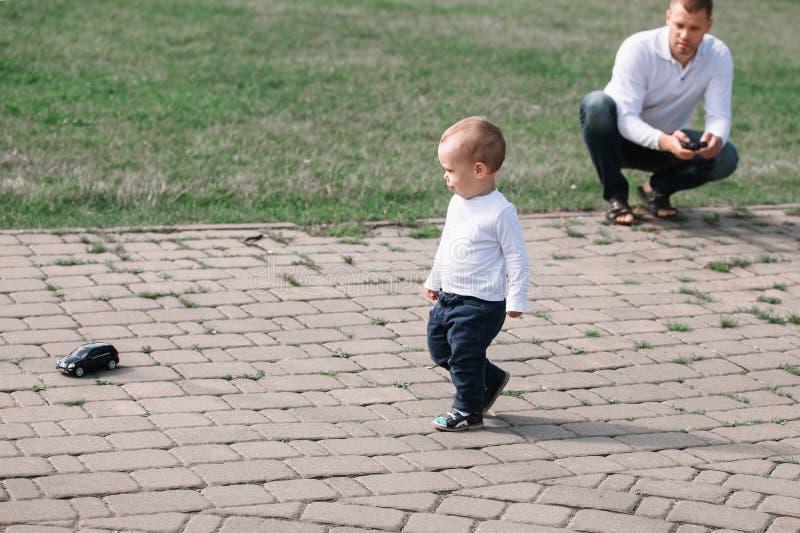 Père regardant son petit fils tout en marchant en parc photographie stock