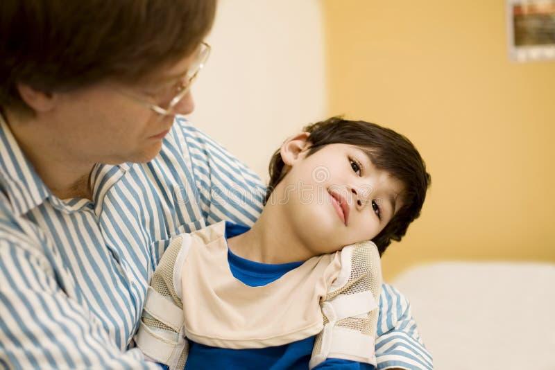 Père retenant le fils handicapé à l'hôpital image libre de droits