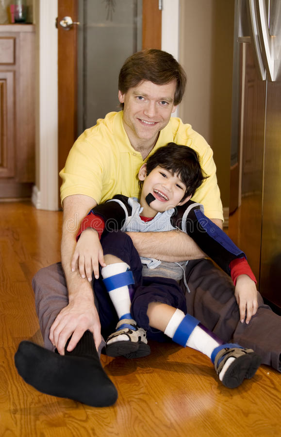 Père retenant le fils handicapé sur l'étage de cuisine images stock