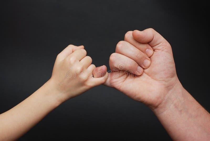 Père tenant la main de fille Relations parentales amicales Fond noir photographie stock