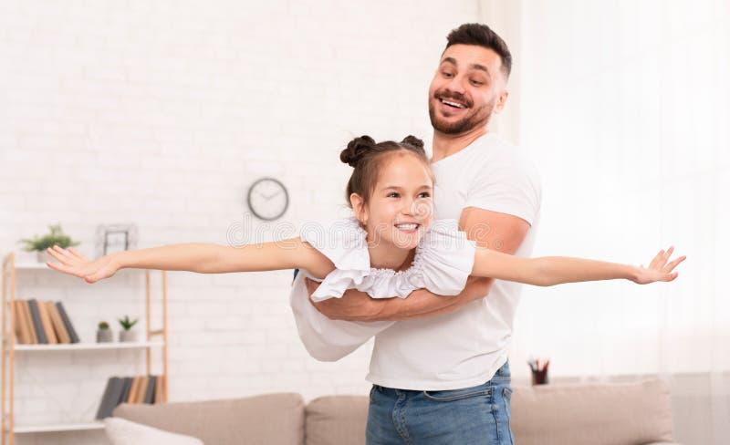 Père tenant sa fille mignonne se trouvant comme l'avion photos stock