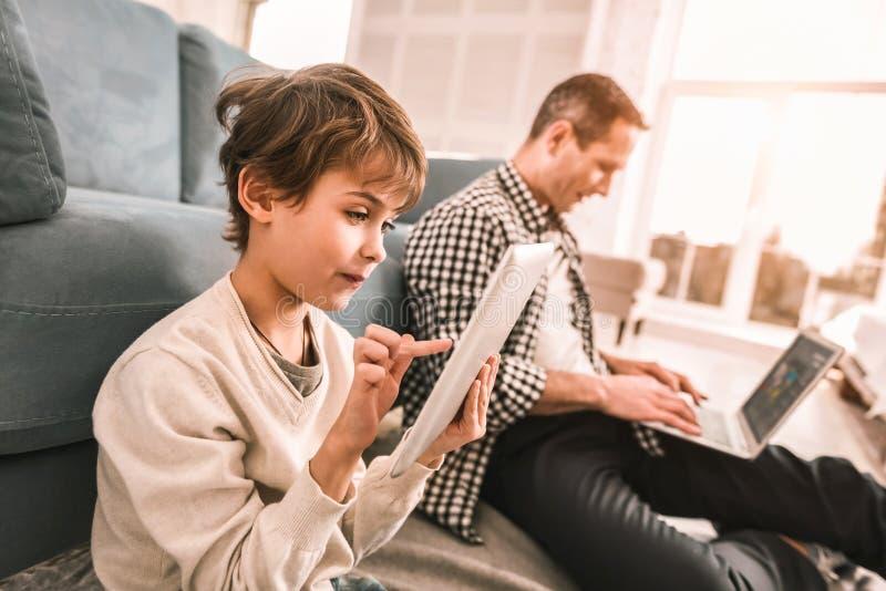 Père travaillant à son ordinateur portable et à son fils jouant sur son comprimé photos libres de droits