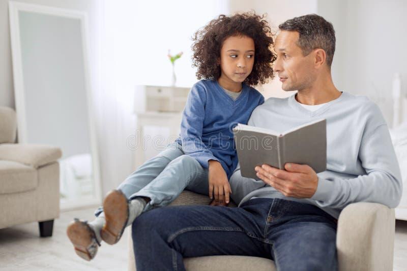 Père vigilant et fille lisant un livre photos libres de droits