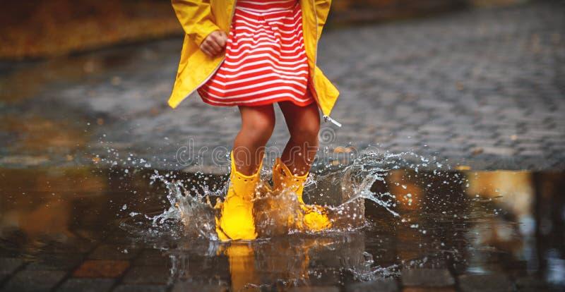 Pé da criança nas botas de borracha na poça na caminhada do outono fotografia de stock