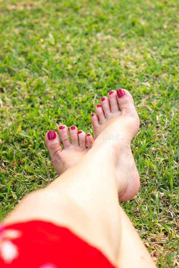 Pé da mulher com o revestimento vermelho do prego na grama verde Conceito do abrandamento fotografia de stock