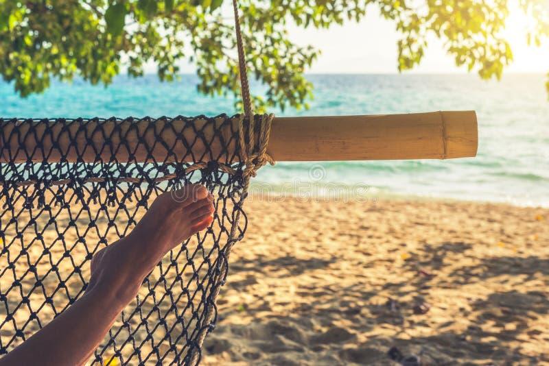 Pé da mulher na rede em uma praia bonita da ilha Conceito do abrandamento dos feriados fotos de stock