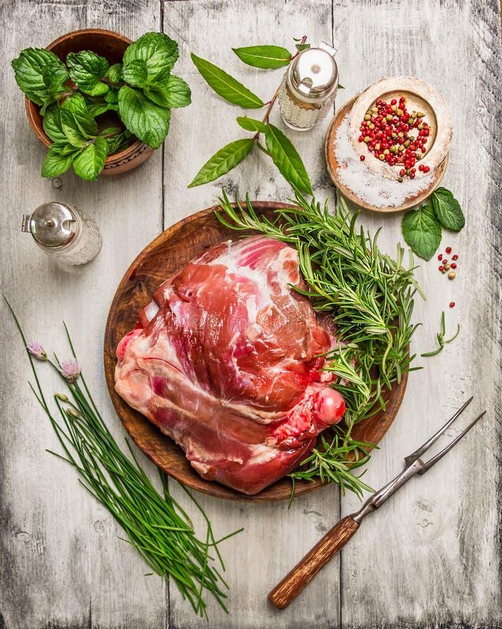 Pé de cordeiro cru com forquilha da carne e de ervas frescas para cozinhar no fundo de madeira branco fotografia de stock