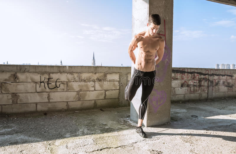 Pé de esticão muscular do Abs apto do homem novo que constrói fora o sunn fotos de stock royalty free