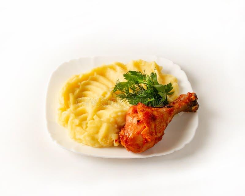 Pé de frango frito apetitoso com batatas trituradas em um close-up da placa em um fundo branco fotografia de stock