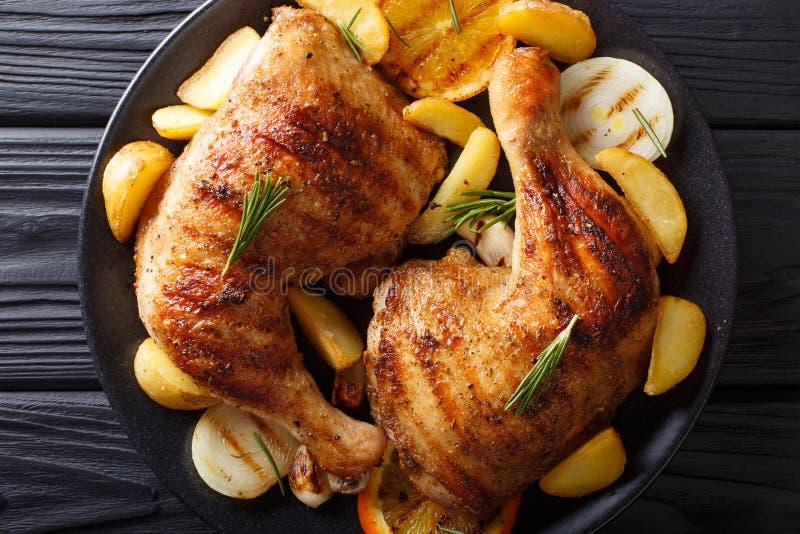 Pé de galinha grelhado com as laranjas, as cebolas e as batatas macro Hor imagem de stock