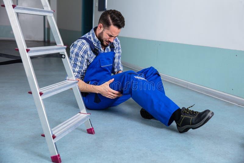 P? de Touching His Injured do trabalhador manual foto de stock royalty free