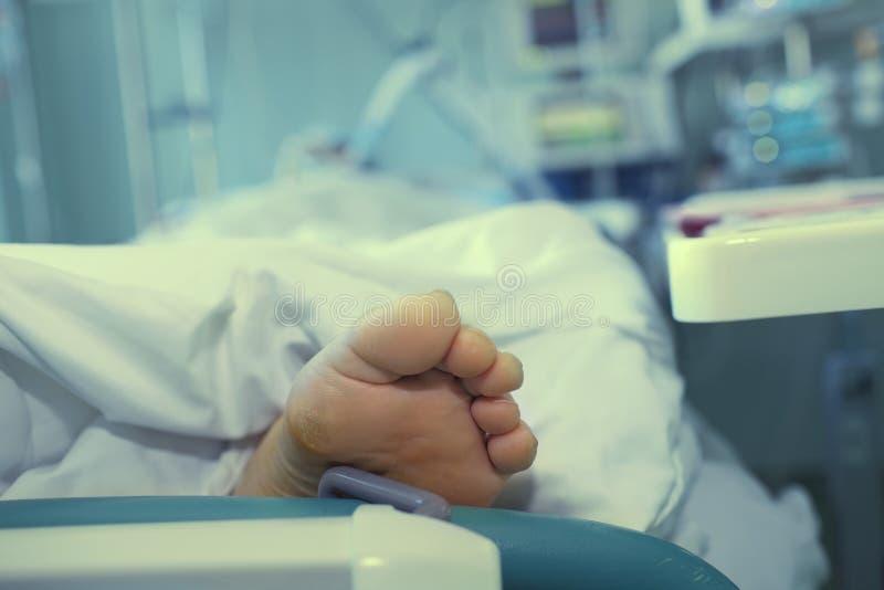 Pé de um paciente de sofrimento em uma cama de hospital como um símbolo da doença fotografia de stock
