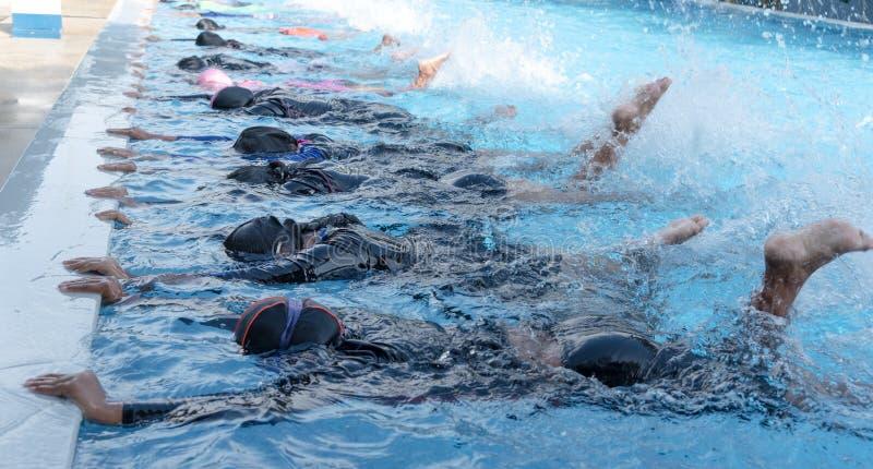 Pé disparado da criança na classe da piscina que aprende nadar fotografia de stock