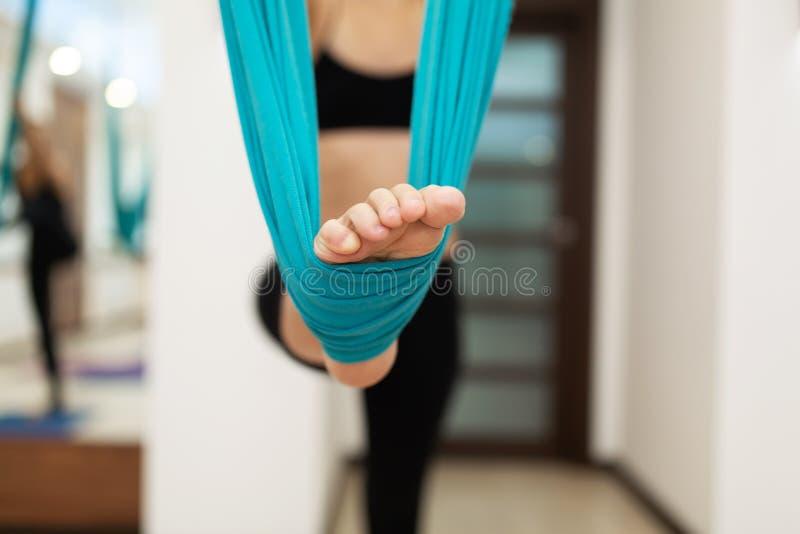 P? do close up na rede para exerc?cios da ioga da mosca Mulher que faz a ioga da mosca que estica exerc?cios no gym Estilo de vid foto de stock